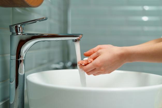 Chiuda in su di una donna che si lava le mani in un lavandino del bagno