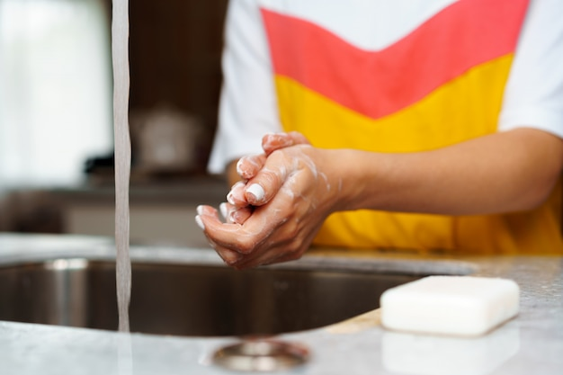 Chiuda in su di una donna che si lava le mani in un lavandino della cucina