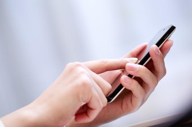 Chiuda in su di una donna che usando smartphone