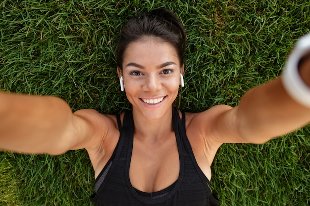 Chiuda in su di una donna felice di forma fisica in cuffie