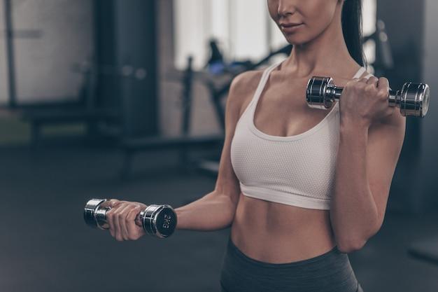 Chiuda in su di una femmina atletica che risolve in ginnastica, sollevando i pesi, copi lo spazio