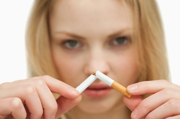 Chiuda in su di una giovane donna che rompe una sigaretta