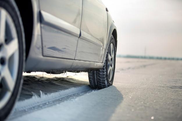 Chiuda in su di una gomma di automobile parcheggiata sulla strada nevosa il giorno di inverno. trasporto e sicurezza.
