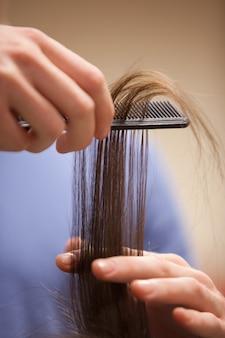 Chiuda in su di una mano che pettina i capelli