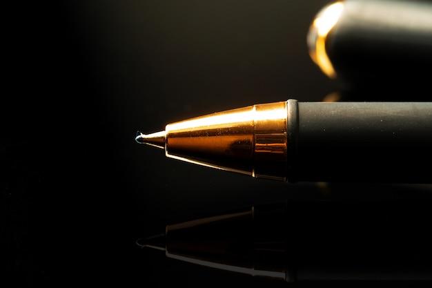 Chiuda in su di una penna su priorità bassa nera