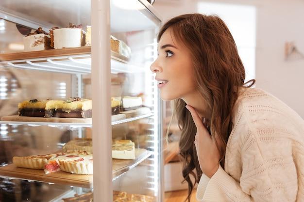 Chiuda in su di una ragazza felice che esamina la pasticceria