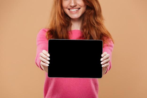 Chiuda in su di una ragazza graziosa sorridente della testarossa che mostra la compressa digitale con lo schermo nero in bianco