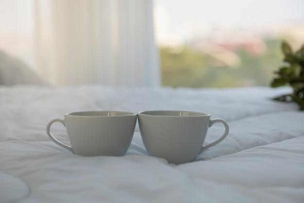 Chiuda in su di una tazza di caffè calda bianca due sul letto in camera da letto con lo spazio della copia di mattina.