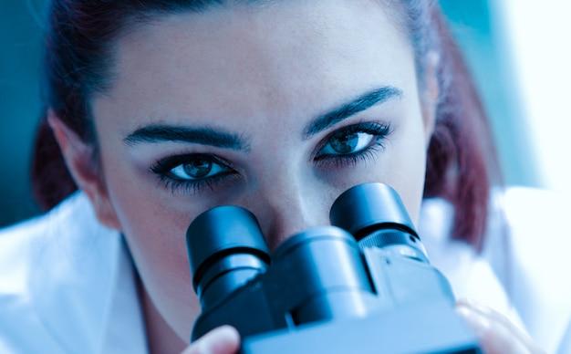 Chiuda in su di uno scienziato che propone con un microscopio