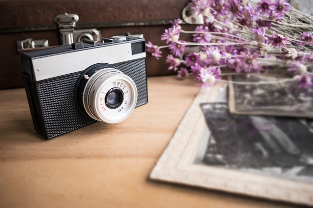 Chiuda in su di vecchio obiettivo di macchina fotografica sopra priorità bassa di vecchia valigia di cuoio