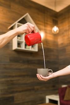Chiuda in su di versamento del latte cotto a vapore nella tazza di caffè