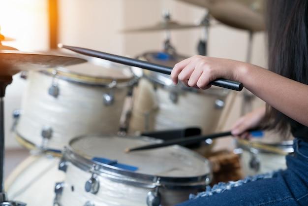 Chiuda in su immagini della ragazza che suona il tamburo.