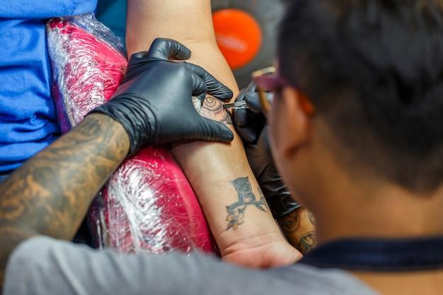 Chiuda in su l'artista del tatuaggio dimostra il processo di ottenere il tatuaggio nero con vernice. il maestro lavora con guanti neri sterili.