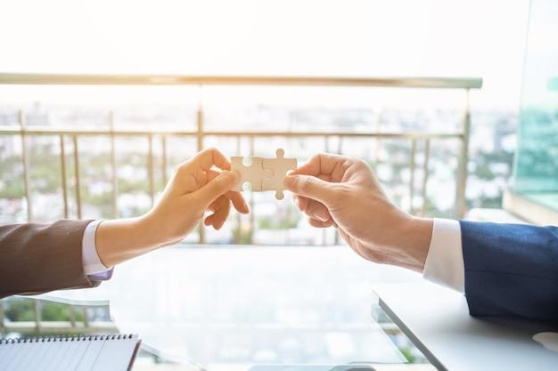 Chiuda in su le mani di rimorchio collegano due jigsaw puzzle. concetto di business, successo e strategia.