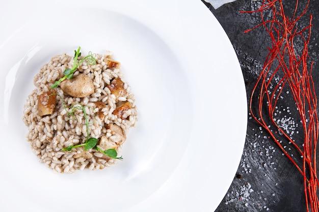 Chiuda in su risotto con funghi porcini e pasta al tartufo in una ciotola bianca. cucina italiana fatta in casa. cibo sano con spazio di copia. sfondo di foto di cibo per menu.