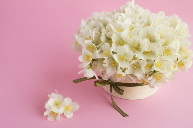 Chiuda in su sui fiori del gelsomino in contenitore di regalo