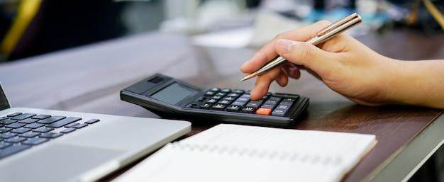 Chiuda in su sul dito dell'uomo dipendente premere sul calcolatore