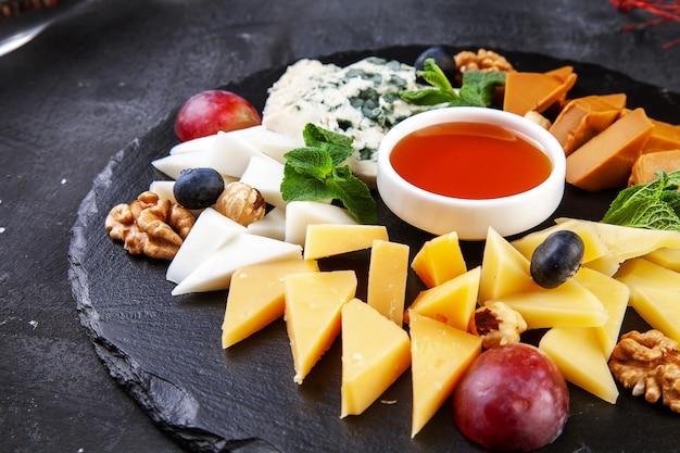 Chiuda in su sul piatto di formaggio servito con le noci, l'uva, il miele. vista dall'alto su diversi tipi di formaggio su oscurità