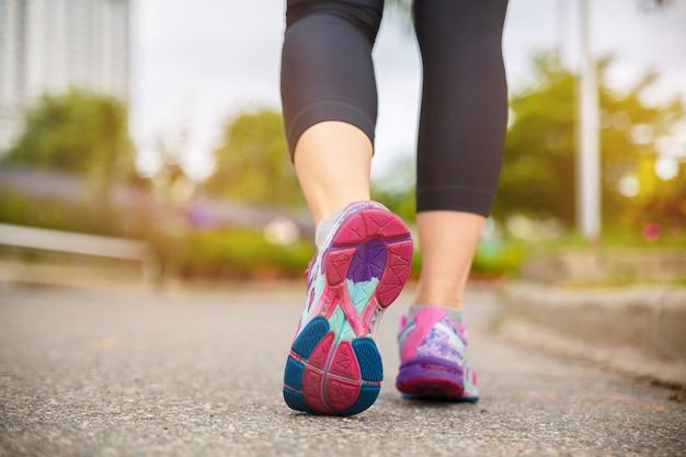 Chiuda in su sulla scarpa, piedi dell'atleta del corridore che corrono sulla strada sotto la luce solare di mattina.