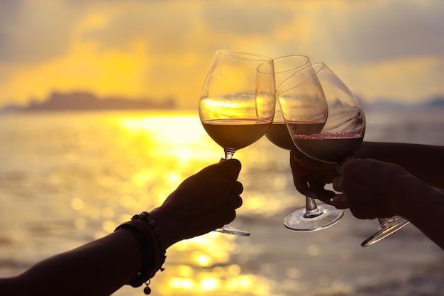 Chiuda in su sulle mani che tengono il bicchiere di vino rosso sulla spiaggia durante il tramonto