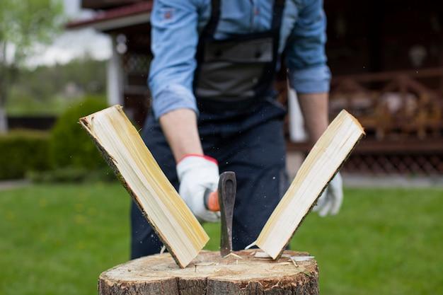 Chiuda in su taglialegna che taglia il legno a pezzi con l'ascia, la segatura vola ai lati, raccogliendo il legno