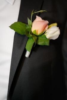 Chiuda in su un'asola dello sposo dalle rose beige
