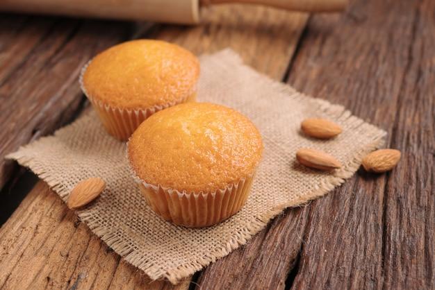 Chiuda in su una tazza della torta della mandorla contro il tessuto del sacco sulla tabella di legno