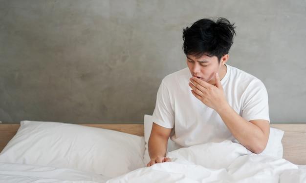 Chiuda in su uomo asiatico assonnato e sbadigliando in camera da letto nel giorno di vacanza