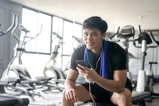 Chiuda in su uomo che tiene smartphone per giocare dopo finire l'esercizio