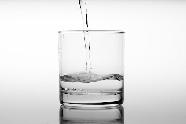 Chiuda in su versando acqua potabile in vetro