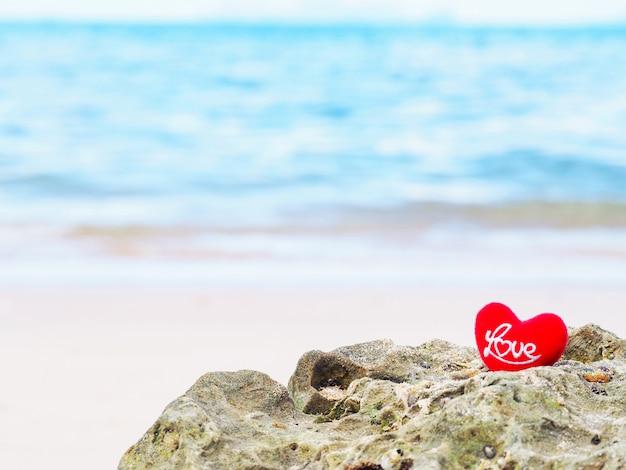 Chiuda su a forma di cuore del cuscino rosso con la lettera amore sulla spiaggia dell'estate.