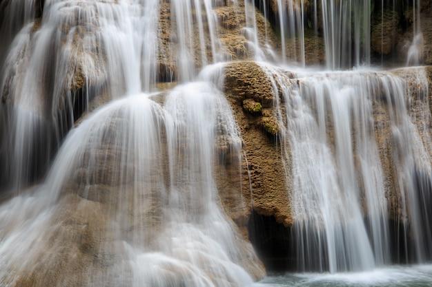 Chiuda su acqua corrente alla cascata di huai mae khamin in foresta profonda, tailandia