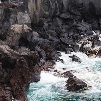 Chiuda su acqua ondulata al puntello roccioso