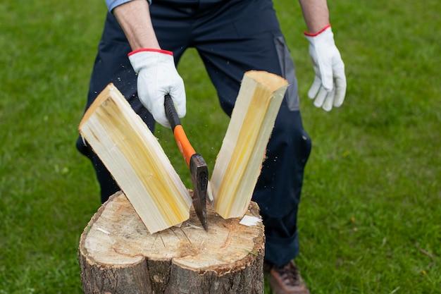 Chiuda su boscaiolo che taglia il legno a pezzi con l'ascia sulla segatura della canapa di legno vola ai lati