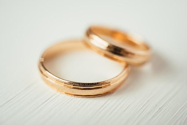 Chiuda su degli anelli di oro di nozze d'intersezione su fondo di legno bianco