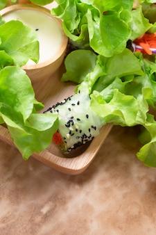 Chiuda su degli involtini primavera fatti a mano freschi della carta di riso del vegano