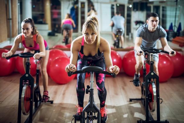 Chiuda su dei giovani concentrati e motivati felici in abiti sportivi con gli asciugamani che guidano la bici di forma fisica in palestra.