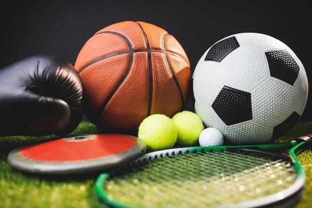 Chiuda su dei guantoni da pugile e palle da golf e discus di tennis di tennis di calcio di pallacanestro