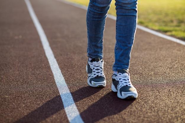 Chiuda su dei piedi della donna in scarpe da tennis e blue jeans di sport sul vicolo corrente sul campo sportivo all'aperto.