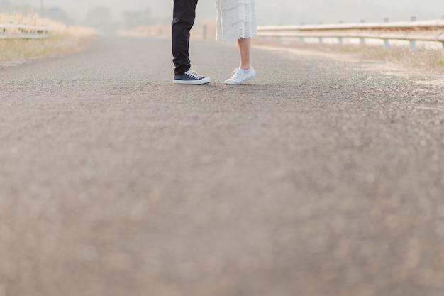 Chiuda su dei piedi e delle casse degli amanti che stanno in mezzo alla strada.