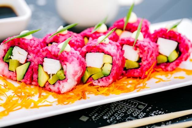 Chiuda su dei rotoli di sushi rosa con i bastoncini di granchio avocado e peperone dolce