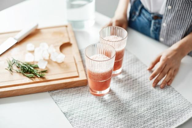 Chiuda su dei vetri delle mani della donna con i pezzi dei rosmarini e del ghiaccio del frullato di dieta della disintossicazione del pompelmo sullo scrittorio di legno.