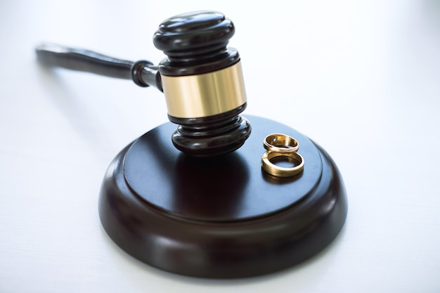 Chiuda su del martelletto del giudice che decide del divorzio di matrimonio e di due anelli dorati del matrimonio