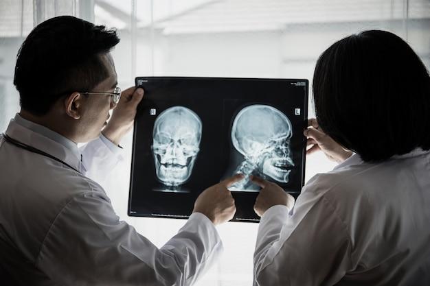 Chiuda su del medico che tiene i raggi x, film dei raggi x del paziente all'ospedale.