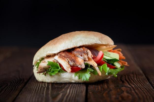 Chiuda su del panino di kebab su fondo di legno