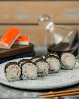Chiuda su del piatto del rotolo di sushi del bastone del granchio di kani maki