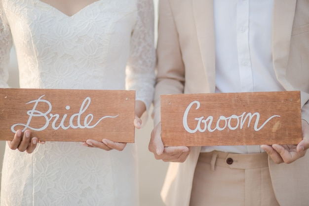 Chiuda su del piatto di legno del segno della tenuta dello sposo e della sposa all'aperto. coppia romantica e concetto di amore