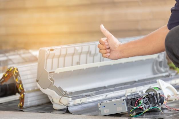 Chiuda su del riparatore che dà il pollice su dopo la pulizia del compartimento del condizionatore d'aria