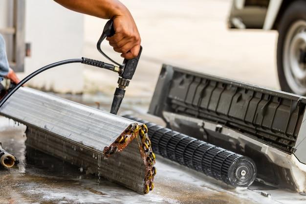 Chiuda su del riparatore che lava il condizionatore d'aria sporco dei compartimenti