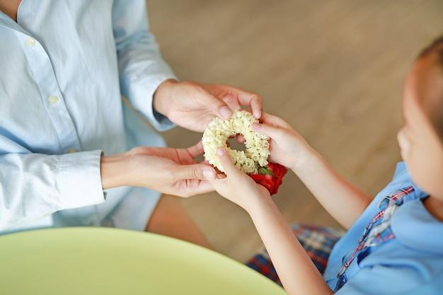 Chiuda su del rispetto asiatico di paga della figlia e dia alla ghirlanda tradizionale tailandese del gelsomino